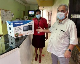 Custos William 'Billy' Shagoury donates a microwave to the May Pen Hospital in Clarendon. Customer Service Manager, Faith Sterling accepts the donation