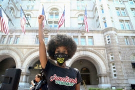 Muka Chisaka, 26, raises her fist in front of Trump International Hotel in Washington D.C. during a Juneteenth Black Lives Matter march on June 19, 2020. (Kaitlin Newman/Zenger)