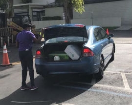 Chairwoman Edmonson helps load food into a resident's trunk at the June 27 drive-through food distribution.