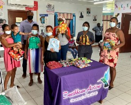 Caribbean Airlines Sales Executive in Guyana Dion Inniss (in back row) was on hand to assist with the distribution  of DFG hygiene kits  to women attending clinic at the Vivienne Health Centre in Linden Guyana on Tuesday April 27, 2021.  DFG's liaison Allison Grant is also in backrow (third right)